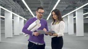 O arquiteto masculino está guardando desenhos e está falando a seu colega fêmea vídeos de arquivo