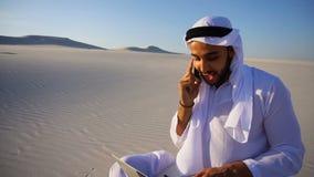 O arquiteto muçulmano bem sucedido do xeique dos UAE do Arabian comunica-se no telefone com o cliente que senta-se na areia com o filme