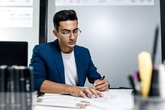 O arquiteto novo de cabelo escuro nos vidros e em um casaco azul está trabalhando com documentos na mesa no escritório fotografia de stock royalty free
