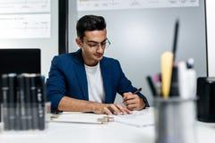 O arquiteto novo de cabelo escuro nos vidros e em um casaco azul está trabalhando com documentos na mesa no escritório imagem de stock royalty free