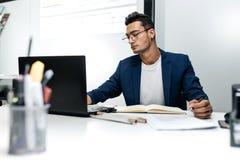 O arquiteto novo de cabelo escuro nos vidros e em um casaco azul está trabalhando com documentos na mesa no escritório fotos de stock