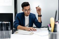 O arquiteto novo de cabelo escuro nos vidros e em um casaco azul está trabalhando com documentos na mesa no escritório imagens de stock
