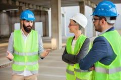 O arquiteto novo farpado está explicando detalhes do projeto e os planos futuros a seus colegas fotografia de stock