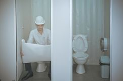 O arquiteto novo sentou-se para baixo para rever o plano quando no toi fotografia de stock royalty free