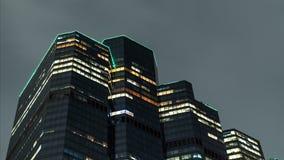 O arranha-céus iluminado close-up na noite de verão, nuvens é refletido na superfície da construção video estoque