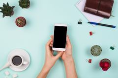 O arranjo flatlay do negócio com ` s da mulher entrega guardar o smartphone com copyspace preto e o outro accessori estacionário  fotografia de stock