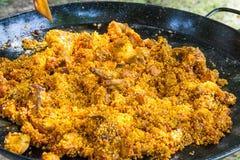 O arroz cru misturou com molho e o azeite fritados de tomate da carne da galinha e do coelho Processo de cozinhar o paella ou o j Imagens de Stock