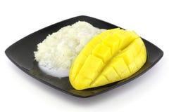 O arroz doce em uma placa um fruto e uma manga doces maduros amarelos do beautifulmango corta com cubos isolou o fundo branco Imagens de Stock Royalty Free