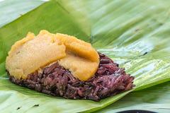 O arroz pegajoso preto com o creme, envolvido na banana sae Imagens de Stock