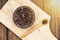 O arroz roxo das grões da baga do arroz na placa de madeira, come o conceito limpo fotos de stock royalty free