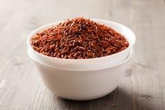 O arroz vermelho em dois empilhou bacias cerâmicas na tabela de madeira Foto de Stock Royalty Free