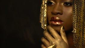 O arstist da composição está aplicando o pulverizador dourado da cor no corpo da mulher africana sedutor bonita com os bordos lus vídeos de arquivo