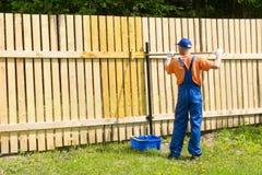O artesão aplica a pintura na parede no jardim usando o rolo da pintura Fotos de Stock