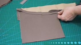 O artesão corta detalhes de matéria têxtil para sacos usando o teste padrão do papet por tesouras vídeos de arquivo