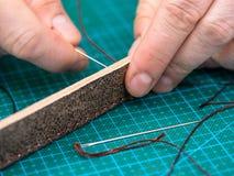 O artesão costura a correia marrom para a bolsa imagem de stock royalty free