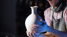 O artesão cria o jarro Homem que guarda o nas mãos após o gerencio ao redor na roda de oleiro Preparação do produto para estufar video estoque