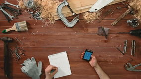 O artesão da vista superior entrega o esboço do desenho do projeto e de usar um smarthphone filme