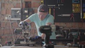 O artesão do retrato nos vidros da proteção que cortam uma placa de madeira com uma circular pequena viu na tabela na oficina video estoque