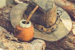 O artesão Handcrafted Yerba Mate Tea Calabash Gourd com Straw Leather Hat na madeira entra Forest Travel Wanderlust Concept fotos de stock