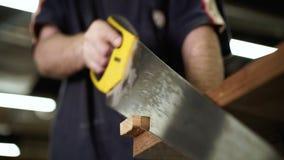 O artesão masculino vê a placa de madeira com serra de vaivém da mão Conceito do woodworking do Handwork video estoque