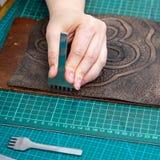O artesão perfura o artigo decorativo para a bolsa fotografia de stock