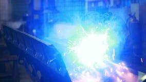 O artesão solda a construção de aço na oficina O metal acende o jogo video estoque
