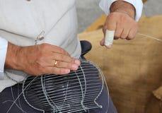 O artesão tece o vaso do fio com mãos Fotos de Stock