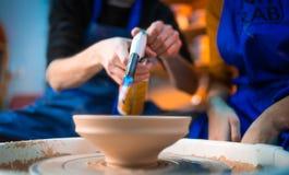 O artesão termina a criação do jarro da argila em sua oficina O homem queima o produto usando a arma do queimador da chama de jat fotos de stock royalty free