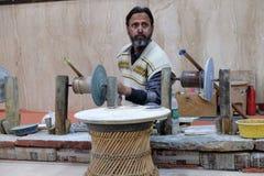 O artesão trabalha em uma oficina que faz o mármore embutido em Agra fotos de stock