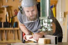 O artesão com a viseira da máscara da segurança segura a serra da faixa na oficina Foto de Stock Royalty Free