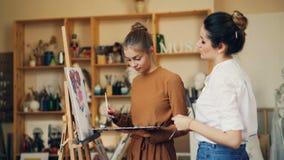 O artista bonito da jovem mulher está ensinando seu estudante pintar as flores que trabalham no estúdio junto com pinturas de óle vídeos de arquivo
