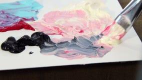 O artista com uma escova mistura a pintura do marfim, a vermelha e a preta na paleta para misturar cores Preparação tirar video estoque