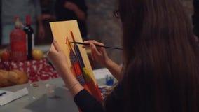 O artista da jovem mulher está pintando a imagem na lona no estúdio da arte filme