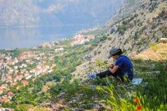 O artista da menina pinta uma paisagem na montanha na cidade de Kotor Foto de Stock Royalty Free
