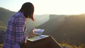 O artista da menina tira pinturas a paisagem das montanhas video estoque