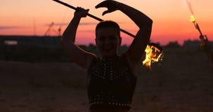 O artista da mostra do fogo respira o fogo na obscuridade na constru??o do abandono, movimento lento Fogo na forma do coração vídeos de arquivo