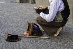 O artista da rua lê mensagens no smartphone fotos de stock