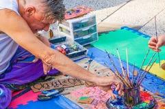 O artista da rua na camisa de t e as calças brilhantes sentam-se no tapete que esvazia pouca garrafa da pintura azul em pires com fotos de stock
