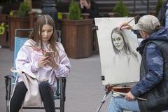 O artista da rua pinta o retrato de uma moça nas ruas de Moscou Fotografia de Stock