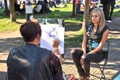 O artista da rua pinta um retrato de uma menina Fotografia de Stock Royalty Free