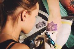 O artista da tatuagem da menina faz a tatuagem em uma mão contra a semelhança azul de uma tatuagem futura usando um esboço Fotografia de Stock Royalty Free
