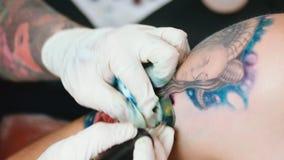 O artista da tatuagem faz a tatuagem vídeos de arquivo