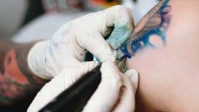 O artista da tatuagem faz a tatuagem no estúdio filme