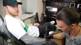 O artista da tatuagem faz a tatuagem no estúdio vídeos de arquivo