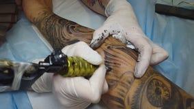 O artista da tatuagem faz a tatuagem no estúdio video estoque