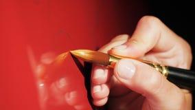 O artista da vista lateral faz a linha amarela com a escova no refrigerador vermelho video estoque