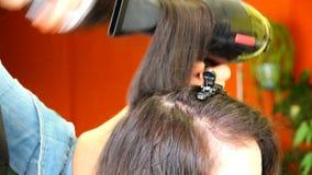 O artista de composição estica e torce o cabelo em sua cabeça, funde o secador de cabelo filme