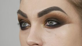 O artista de composição profissional faz à composição os olhos fumarentos da máscara marrom de um modelo bonito com olhos verdes  filme