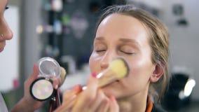 O artista de composição que faz a composição acentua usando sombras brilhantes Pondo sobre a cara, o nariz usando os dedos e uma  vídeos de arquivo