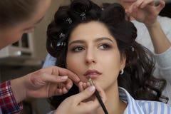O artista de composição que faz uma composição para a noiva O maquilhador aplica o batom vermelho Face bonita da mulher Mão da co imagens de stock royalty free